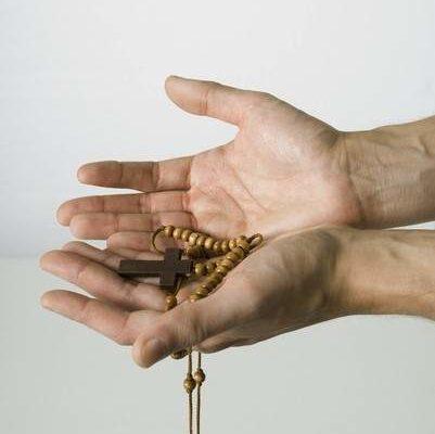 manos con rosario
