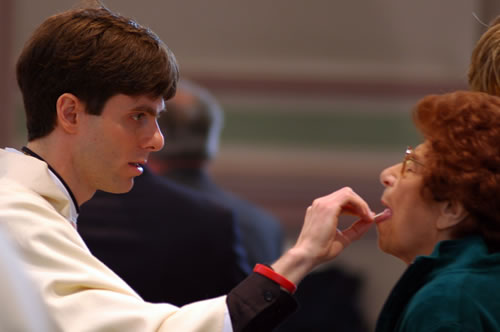 señora recibiendo la comunion de un seminarista